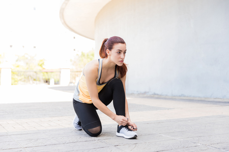 Beautiful woman tying her shoes and getting ready to workout in city