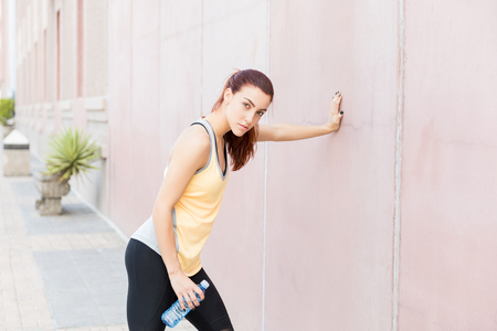 Tired determined woman leaning on wall after her routine training