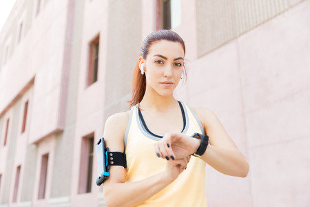 Portrait of runner checking heart rate on smartwatch after jogging in city 스톡 콘텐츠