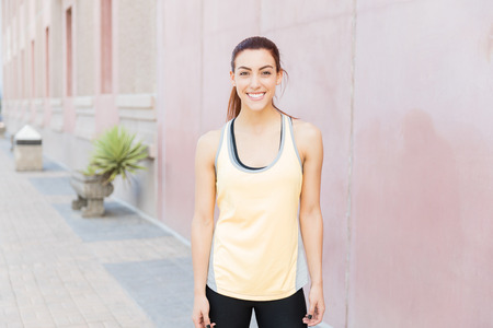 Portrait of attractive smiling athlete standing on sidewalk in city