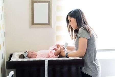 Vista lateral de la madre cambiando el pañal del bebé en casa