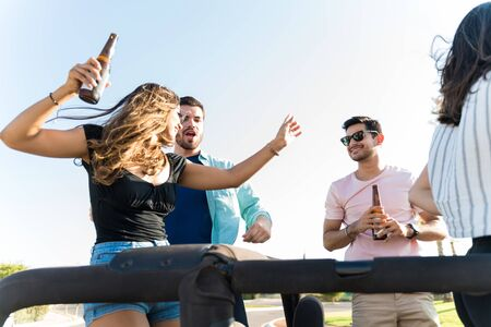 Young pals dancing and enjoying music with beer on road trip in summer Standard-Bild