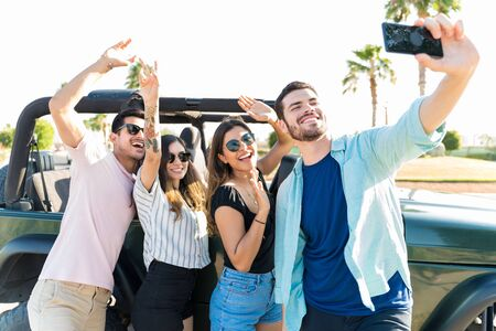 Young man taking selfie with happy friends by SUV in summer vacation