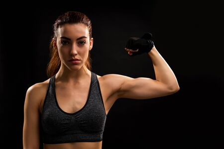 Portrait of young Caucasian female athlete flexing muscles while standing against isolated background