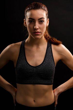 Porträt einer selbstbewussten jungen, fitten Frau, die mit den Händen auf der Hüfte vor schwarzem Hintergrund steht Standard-Bild
