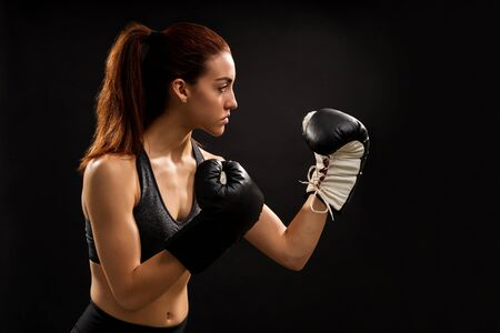 Young woman practicing boxing against isolated background