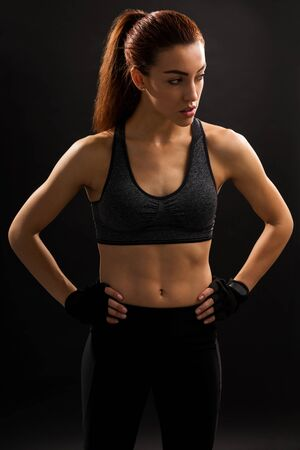 Confident beautiful woman with tight abs in sportswear against plain background