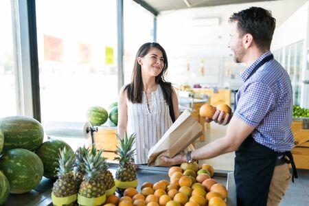 Propietario de comestibles masculino envasado de naranjas en bolsa de papel mientras habla con la clienta en el puesto de frutas en el mercado orgánico