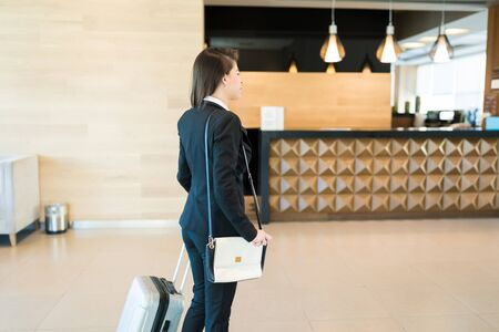 Side view of Latin businesswoman with purse pulling suitcase while arriving at hotel lobby on business trip Foto de archivo