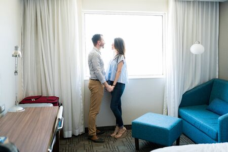 Full length side view of mid adult newlywed couple holding hands and talking while standing by window in room Фото со стока