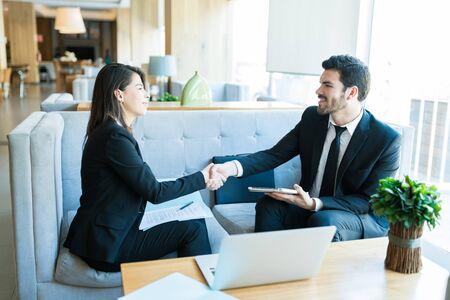 Lächelnde Geschäftsleute, die während des Treffens in der Lobby mit Handschlag gratulieren Standard-Bild