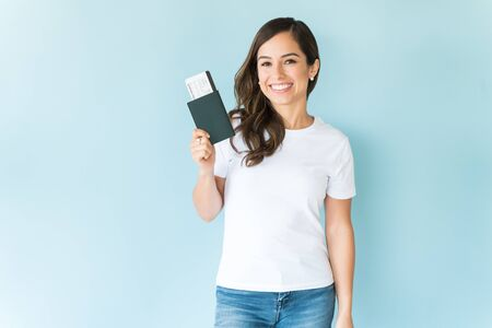 色の背景に隔離されたパスポートを持つ幸せなかわいい女性観光客
