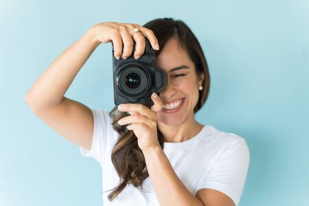 Caucasian attractive female clicking with DSLR camera over plain background