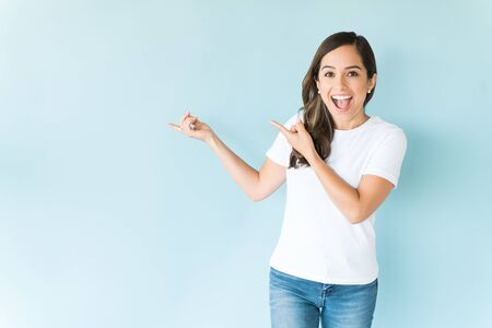 Excited mid adult woman with open mouth showing space on colored background 写真素材 - 128326122