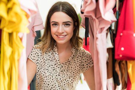 Mooie blanke vrouw die geniet van winkelen terwijl ze gluurt door topjes die in de winkel hangen Stockfoto