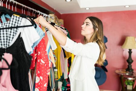 Caucasian female manager with brown hair arranging clothes on rack in shopping mall boutique