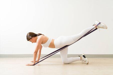 Vista lateral de longitud completa de una mujer joven dedicada en forma que hace arrodillado butt blaster con banda de resistencia en el estudio de yoga