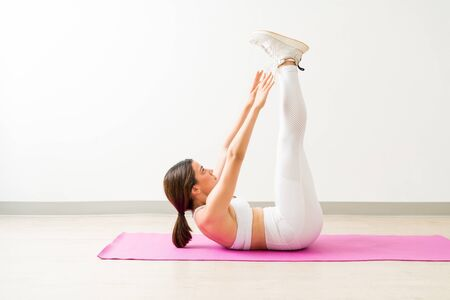 Full length side view of dedicated young woman raised leg crunches on yoga mat during fitness training