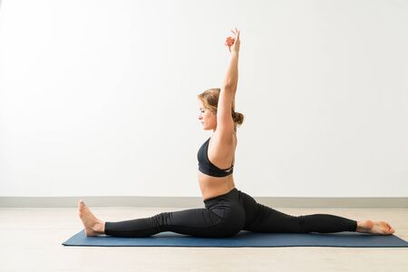Slim fit brunette female doing splits and practicing Hanumanasana at training studio