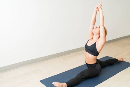 Confident young Caucasian woman sitting in Hanumanasana on mat by wall Stockfoto