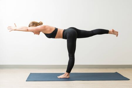 Full length of healthy young woman training in Warrior Pose III on mat in yoga studio