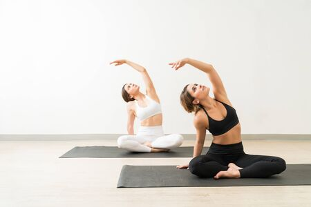 Beautiful young women practicing side bend pose on exercise mats against wall during workout