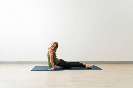 Full length side view of young woman practicing Urdhva Mukha Shvanasana by wall at yoga studio Фото со стока - 128773009