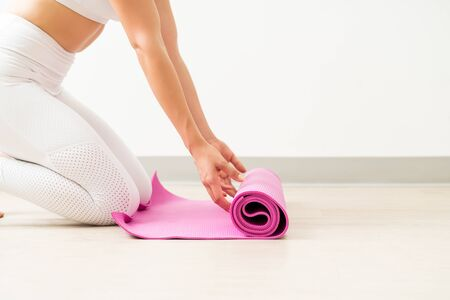 Midsection of young woman opening pink exercise mat for yoga during fitness training in studio