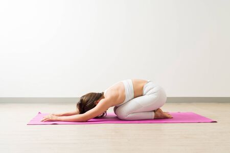 Full length side view of brunette female in sportswear practicing Balasana at fitness studio