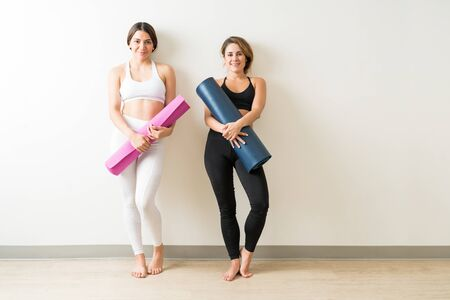 Portrait of beautiful young women holding exercise mats while leaning on white wall in yoga studio Фото со стока