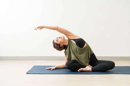 Attractive young woman looking up while exercising side bend pose on yoga mat against wall during workout training