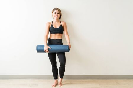 Full length portrait of beautiful young woman holding exercise mat against white wall in yoga studio