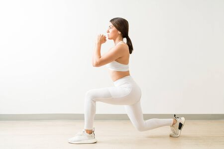 Confident young attractive fit woman doing low lunge exercise at yoga studio Фото со стока - 128773044