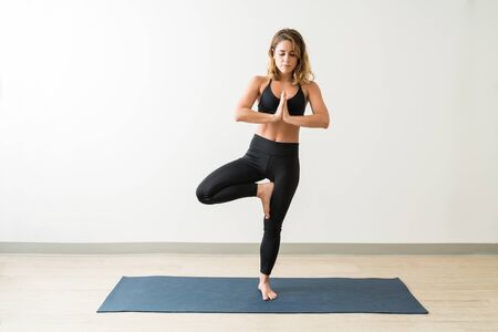 Beautiful young brunette female meditating while practicing Vriksasana against wall in yoga studio Фото со стока