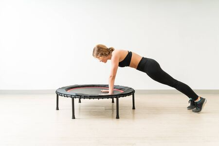 Side view of determined female doing push ups on trampoline by wall during fitness training at studio