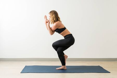 Full length side view of flexible young brunette woman performing Garudasana by wall during fitness training