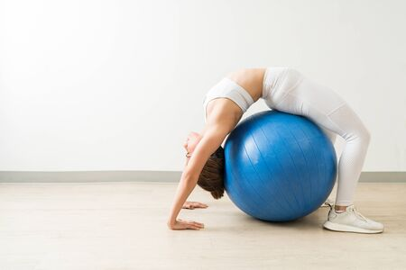 Side view of flexible female stretching back on fitness ball during training at studio Фото со стока - 128773070