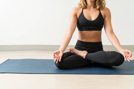 Low section of female meditating while practicing Padmasana on mat against wall Фото со стока - 128773072