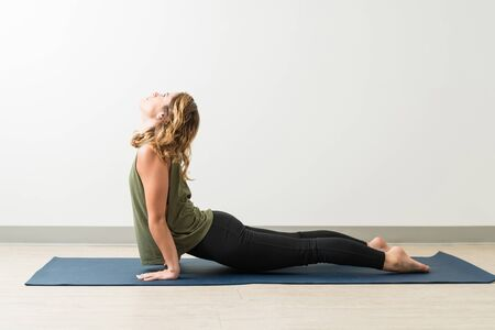 Young Caucasian female with Upward Facing Dog Pose on mat in studio
