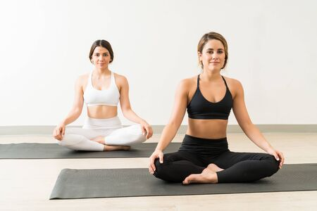 Portrait of confident young attractive females relaxing while doing Sukhasana against wall at yoga studio Фото со стока