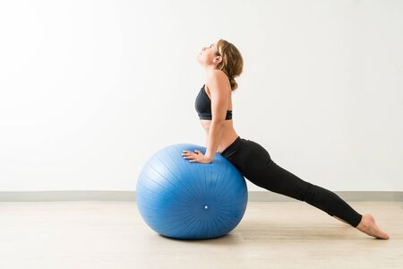 Pretty brunette female exercising while leaning on fitness ball at training studio
