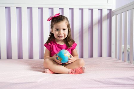 Smiling cute girl playing with inflatable globe ball on bed in bedroom