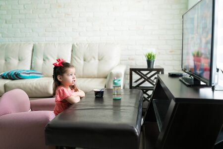 Toddler girl watching television in living room at home