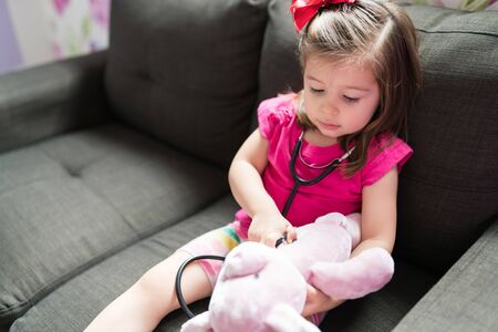 Little girl pretending to be doctor while treating her stuffed toy with stethoscope on sofa in living room at home