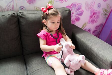 Female toddler imitating as doctor while playing with teddybear on sofa at home