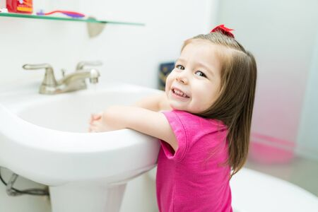 Cheerful female kid washing hands in bathroom sink during morning routine at home