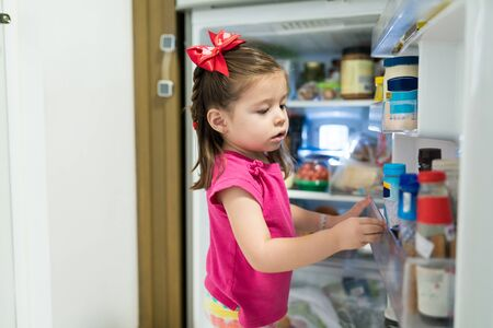 Cute little curious girl searching in refrigerator at home