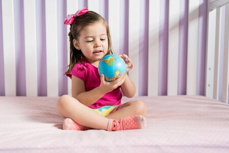 Charming playful toddler looking at globe ball on bed in bedroom at home