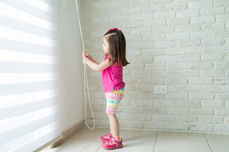 Side view of small girl opening blinds of window at home