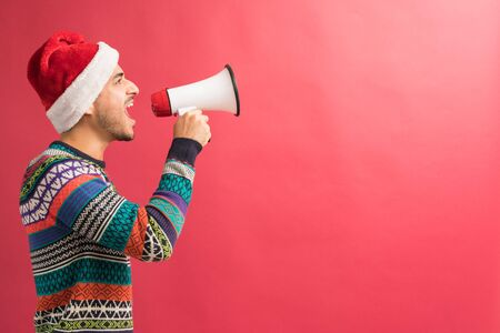 Side view of confident young Hispanic man shouting announcement through megaphone isolated in studio Banque d'images - 129016282
